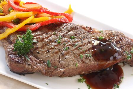 Grilled strip or porterhouse grain-fed beef steak, with colorful vegetables and an onion gravy. photo