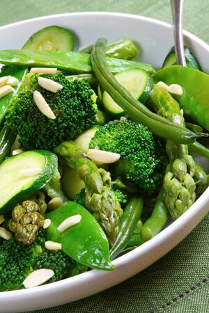 Serving bowl of mixed green vegetables, topped with toasted almonds.  Delicious healthy eating. photo