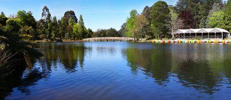 arching: Panorama de un lago, con buques, paddleboats, arqueo y un puente. Glorioso sol de primavera. Foto de archivo