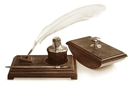 Vintage writing set, including feather quill pen, nib pen, ink well and blotter, on writing stand.  Isolated on white.