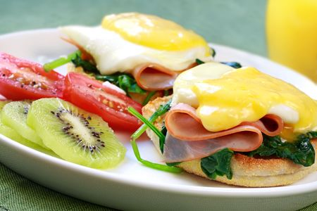 poached: Eggs benedict.  Toasted muffins topped with spinach, ham, a poached egg, and Hollandaise sauce.  Accompanied by fruit and juice.  Delicious!