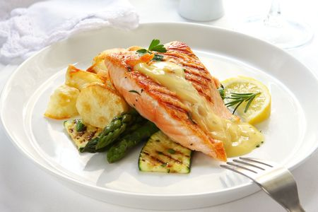 topped: Atlantic salmon grilled to perfection, over potatoes, asparagus and grilled courgette.  Topped with hollandaise sauce. Stock Photo