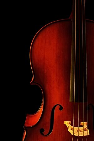stringed instrument: Cello, in close-up with black background.  Natural warm light.