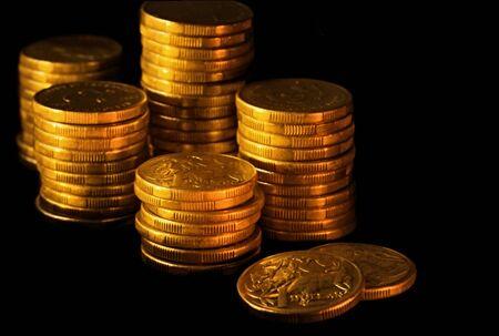 australian dollars: Stacks of Australian dollars in golden light, on black background.