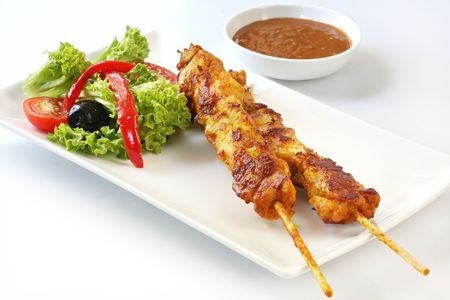 Chicken kebabs and salad.  Skewed satay chicken, with satay sauce. photo