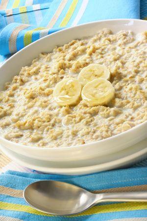 Bowl of porridge, with banana and honey.  A sunny, healthy oatmeal breakfast. photo