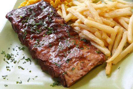 BBQ marinated spareribs and fries, with sweet corn.   photo