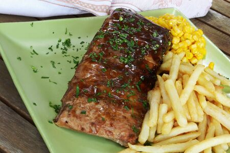 Barbecued pork spareribs on outdoor table, with fries and sweet corn. photo