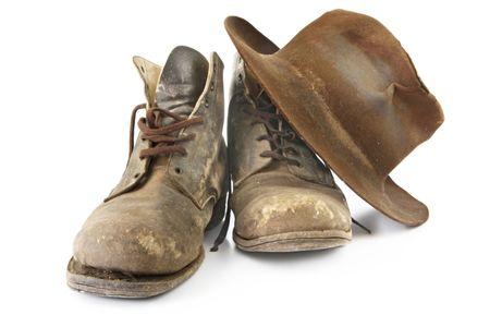 zapatos de seguridad: Maltratadas, desde botas de trabajo y sombrero de fieltro, aislados en blanco. Usado continuamente desde los a�os 1940! Foto de archivo