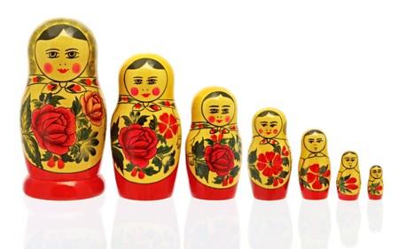 mu�ecas rusas: BABUSHKA Rusia de anidaci�n de las mu�ecas, aislados en blanco. Reflejada en la superficie de cristal. Foto de archivo