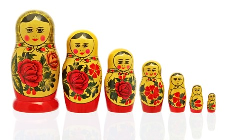 russian nesting dolls: Russian Babushka nesting dolls, isolated on white.  Reflected on glass surface. Stock Photo