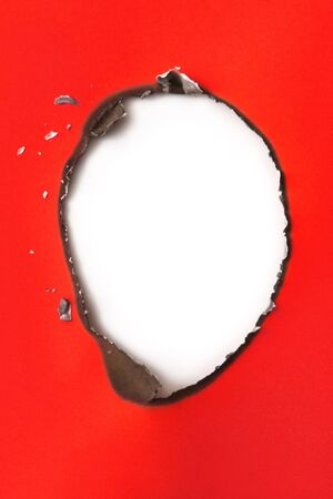 Burn hole in red paper, casting shadow on white beneath.   photo