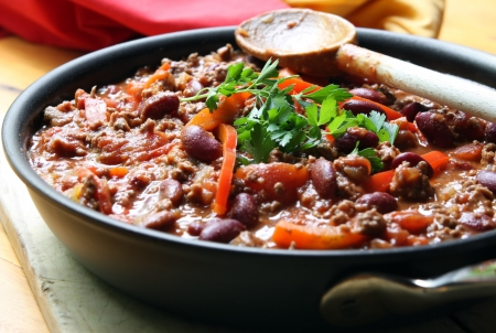 A pan of chilli, ready to serve.  Soft focus, shallow depth of field. Stock Photo