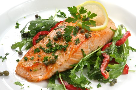 Atlantic salmon with a rocket salad, garnished with lemon, capers and parsley. photo