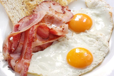 Breakfast of bacon and eggs with wholegrain toast.  Close-up view.