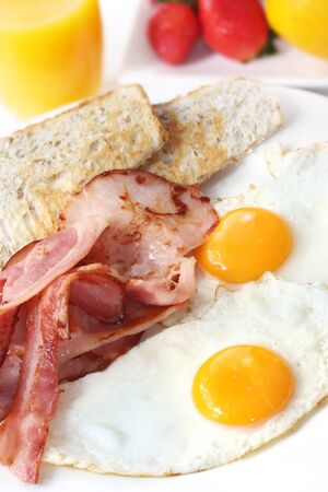 Bacon and eggs for breakfast, with toast, orange juice and fresh fruit. Stock Photo - 4027330