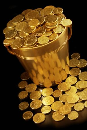 Bucket of golden coins, with black background and warm lighting.