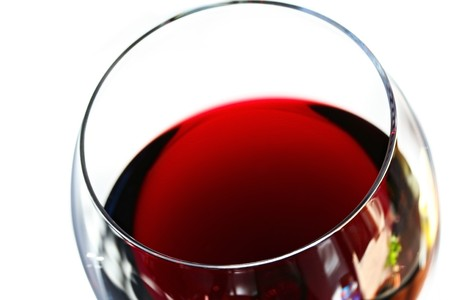 Glass of red wine, in close-up with white background.  Soft focus. photo