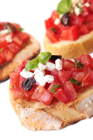 crusty: Bruschetta - crusty toast topped with diced tomatoes, black olives, goats cheese and basil. Stock Photo