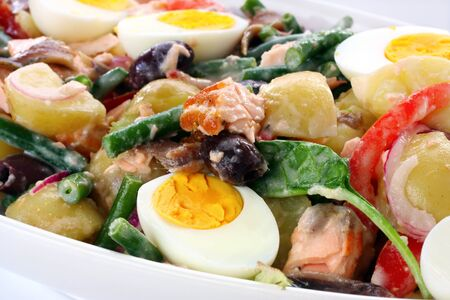 Salad Nicoise.  Beans, potatoes, tomatoes, eggs, black olives, red onion, anchovies, and flaked salmon. photo