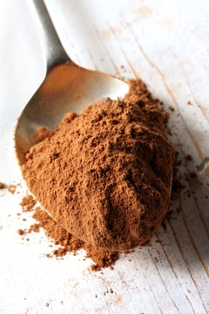 chocolate powder: Cocoa powder on an old silver spoon, on rough wooden surface.