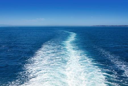 Tras barco en el mar, en un brillante día soleado. Esta es la vista detrás de un transbordador de automóviles.