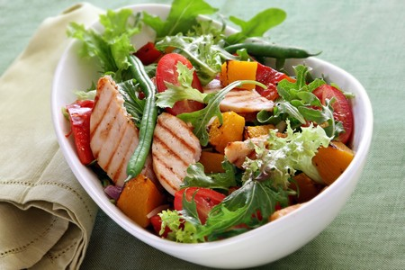 Chicken salad with roasted vegetables and mixed greens. Delicious healthy eating. Stock Photo