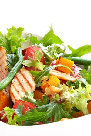 Chicken salad with roasted vegetables and mixed greens. Delicious healthy eating. photo