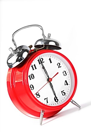 beat the clock: Red alarm clock set to 6.00am.  Natural early morning light.