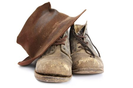 Old 1940s work boots and battered felt hat, isolated on white.  Used until recent years.  According to their owner, all the boots need is another resole, and theyll be fine for a while yet! photo