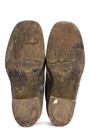 and worn out: Worn soles of old workboots, isolated on white.  These boots have been worn since the 1940s.