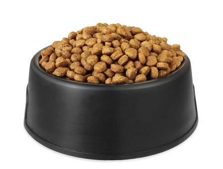 pet food: Dry dog food in a black dog dish, isolated on white.