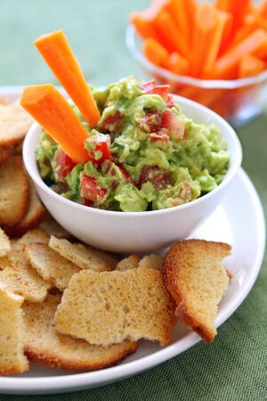 guacamole: Avocado guacamole served with carrot sticks and bagel crisps - a healthy variation of this delicious snack. Stock Photo