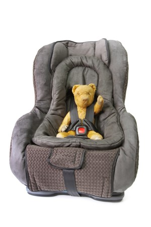 car front view: Vintage teddy bear strapped into baby car seat, isolated on white.  This car seat is suitable from birth, convertible from rear facing to front facing.