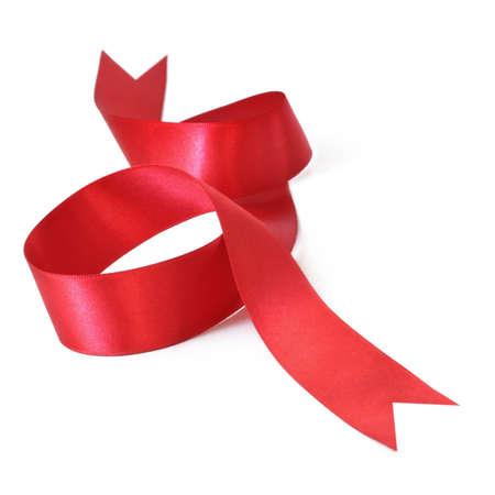 Red satin ribbon curled up on white surface, casting natural shadow. photo