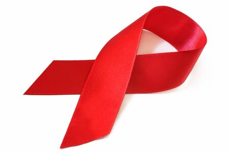 hiv aids: Red satin AIDs awareness ribbon, over white with soft shadow. Stock Photo
