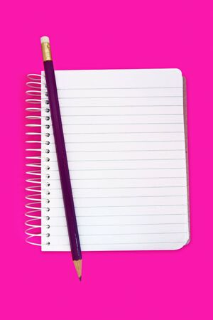 Spiral notebook with a pencil, over neon pink background. Stock Photo - 4267473