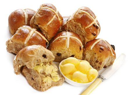 Hot cross buns, with a dish of butter curls and vintage knife.  A delicious Easter treat. photo