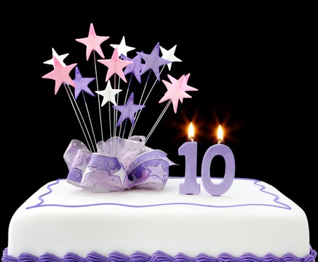 white candle: Fancy cake with number 10 candles.  Decorated with star-shapes and ribbons, in pastel tones.