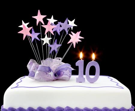 torta candeline: Fancy torta con il numero 10 candele. Decorato con la stella di forme e nastri, in toni pastello. Archivio Fotografico
