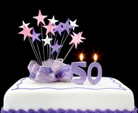 Fancy cake with number 50 candles.  Decorated with ribbons and star-shapes, in pastel tones on black background.