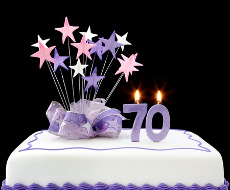 birthday cake: Fancy cake with number 70 candles.  Decorated with ribbons and star-shapes, in pastel tones on black background.