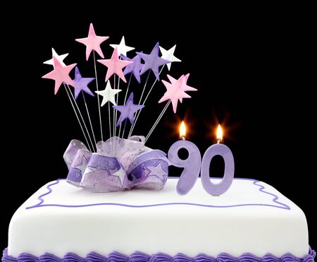 Fancy cake with number 90 candles.  Decorated with ribbon and star-shapes, in pastel tones on black background. photo
