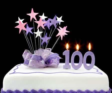 Fancy cake with number 100 candles.  Decorated with ribbons and star-shapes in pastel tones against black background.