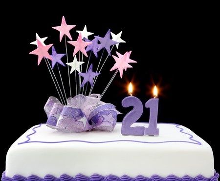 21: Cake with number 21 candles.  Decorated with ribbons and star-shapes, in pastel tones over black background.