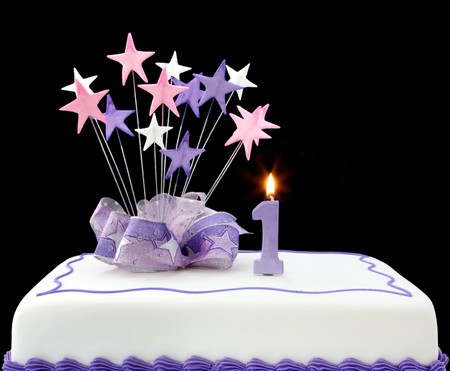 first birthday: Fancy cake with number one candle.  Decorated with ribbons and star-shapes, in pastel tones on black background. Stock Photo