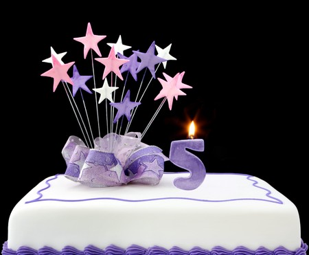 Fancy cake with number 5 candles.  Decorated with ribbons and star shapes, in pastel tones over black background.
