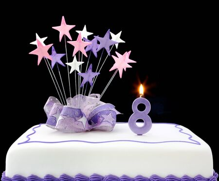Fancy cake with number 8 candle.  Decorated with ribbons and star-shapes, in pastel tones over black background.
