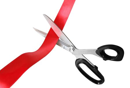 Scissors cutting through red ribbon or tape, isolated on white. photo