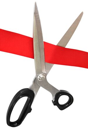 cutting through: Scissors cutting through red tape.  Isolated on white.